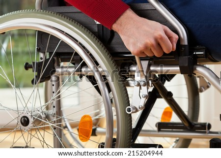 Close-up of disabled man using wheelchair breaks  - stock photo