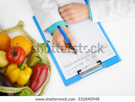 Close-up of doctor diettian hands with pen prescribing treatment. Female physician filling medical history form in the office.  - stock photo