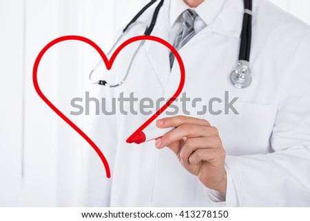 Close-up Of Doctor Hand Drawing A Heart Symbol With Red Marker - stock photo