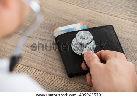 Close-up Of Doctor Hand Examining A Wallet With Stethoscope On Wooden Desk In Clinic - stock photo