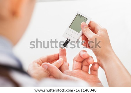 Close-up Of Doctor Holding Patient's Finger Checking Sugar Level - stock photo
