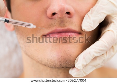 Close-up Of Doctor In Glove Giving Injection On Face Of Man In Clinic - stock photo