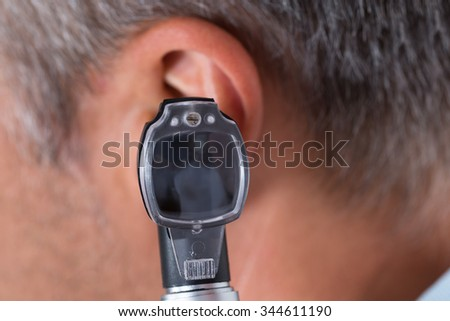 Close-up Of Doctor Looking Through Otoscope In Man's Ear - stock photo