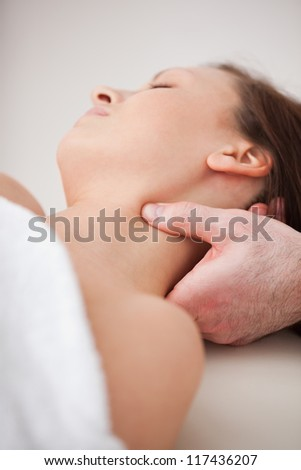 Close-up of doctor pressing his thumb on the neck of his patient indoors