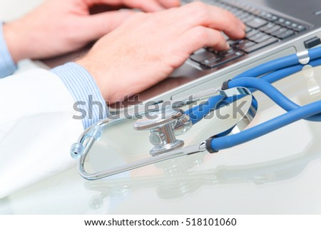 Close up of doctor's hands typing on a laptop with stethoscope in the foreground
