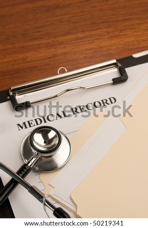 Close up of doctor's stethoscope on patient's medical record. - stock photo
