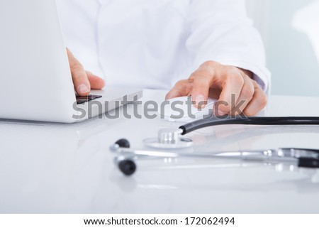 Close-up Of Doctor Using Laptop In Front Of Stethoscope At Desk - stock photo