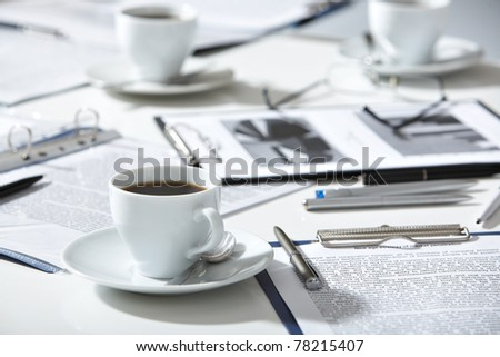 Close-up of documents, pen, cup of coffee on the table - stock photo