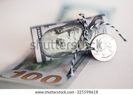 Close-up of dollars roll with twenty five cent coin - stock photo