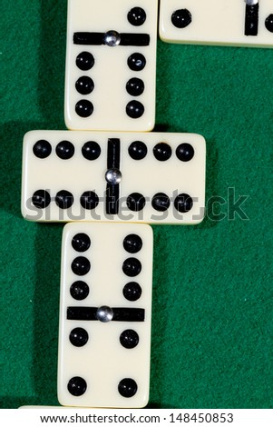 Close up of domino pieces with black dots in green table