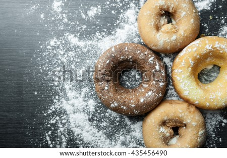 Close up of donuts with icing. Top view of chocolate donuts with icing sugar on black wooden background. Flat lay donuts. Copy space. - stock photo