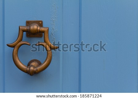 Close up of door handle with an old double wood door painted with blue - stock photo