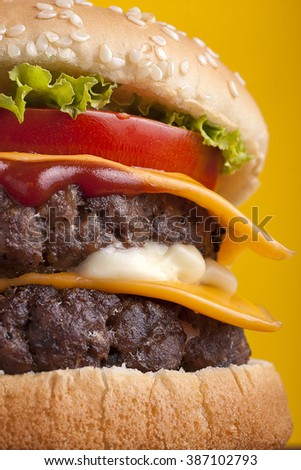 Close up of Double Cheeseburger on  yellow background.