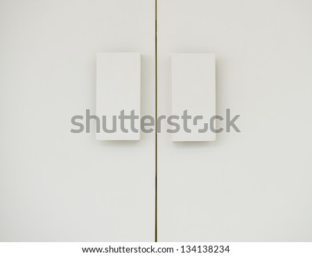 Close up of double door handle on the white door. - stock photo