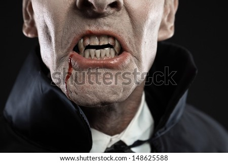Close-up of dracula with black cape showing his scary teeth. Vamp fangs. Studio shot against black. - stock photo