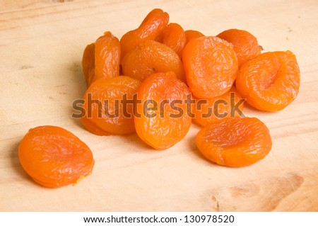 close up of dried apricots on wooden table - stock photo