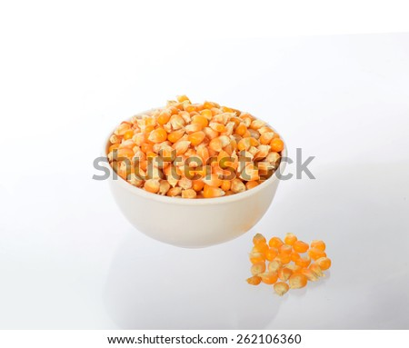 Close Up of Dried corn in bowl with heap used for making popcorn  - stock photo