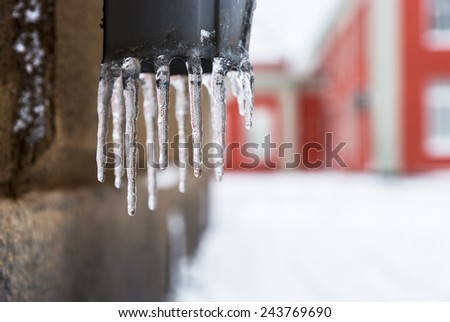 close up of dripping icicles on draining pipe - stock photo