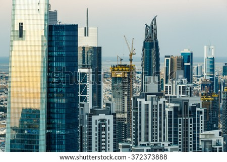 Close up of Dubai's business bay towers at sunset. Rooftop view of some skyscrapers and new towers under construction.  - stock photo