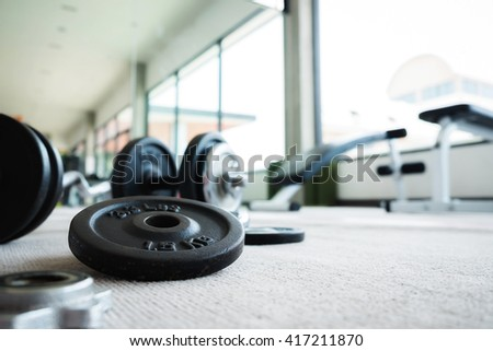 Close up of dumbbell exercise weights on the floor at fitness gym with copy space. - stock photo