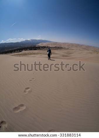 Close up of dune with backpacker walking away shows footprints on otherwise pristine dune.  Taken at Great Sand Dunes National Park in Colorado - stock photo