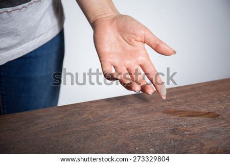 Close-up of dust on woman finger taken from wooden table - stock photo