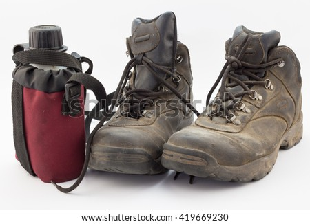 Close up of dusty hiking boots and red water bottle isolated on white