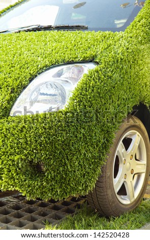 Close up of Eco car covered with artificial green grass - stock photo