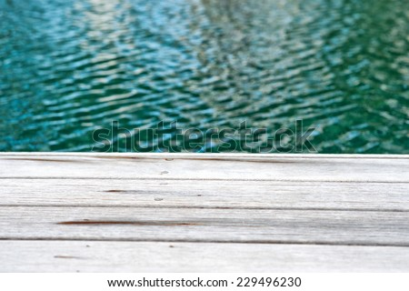 Close Up of Edge of Wooden Decking Surrounding Swimming Pool - stock photo