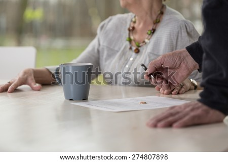 Close-up of elder man signing divorce documents - stock photo