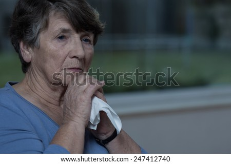 Close-up of elderly crushed lady with tissue - stock photo