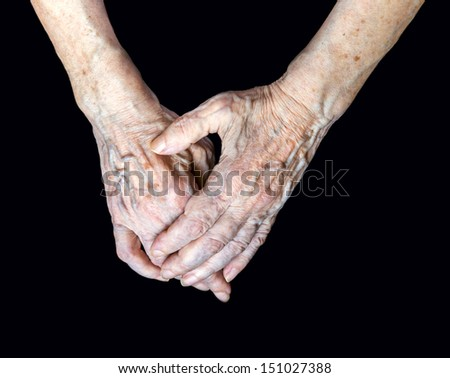 Close up of elderly female hands on black background - stock photo