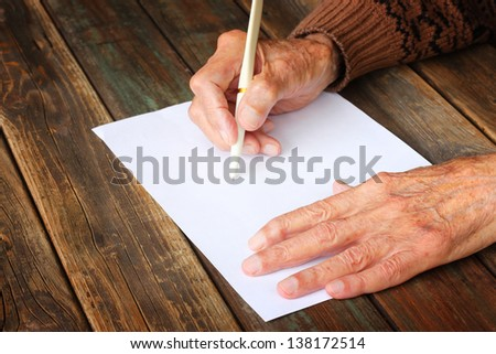 close up of elderly male hands on wooden table . writing on blank paper - stock photo