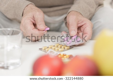 Close up of elderly man holding packaging of tablet pills - stock photo