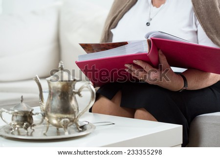 Close-up of elderly woman browsing the photo album - stock photo