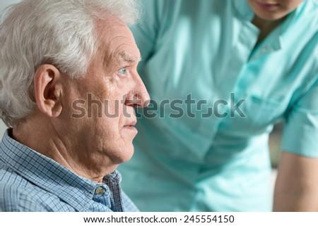 Close-up of elderly worried sick man sitting with nurse - stock photo