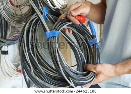 Close Up Of Electrician Fitting Wiring On Construction Site - stock photo