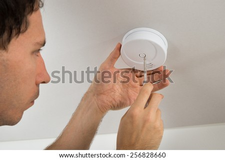 Close-up Of Electrician With Screwdriver Repairing Fire Sensor - stock photo