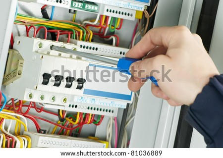 Close-up of electrician work on a industrial panel mounting and assembling new wiring - stock photo