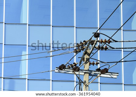 close-up of electricity pole with the glass building background