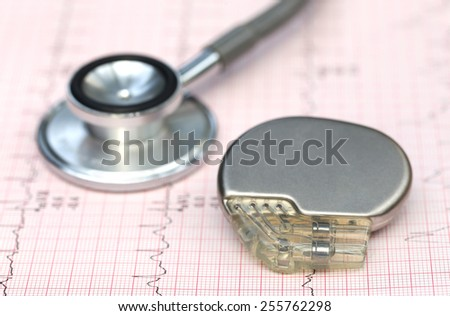 Close up of electrocardiograph with stethoscope and pacemaker - stock photo