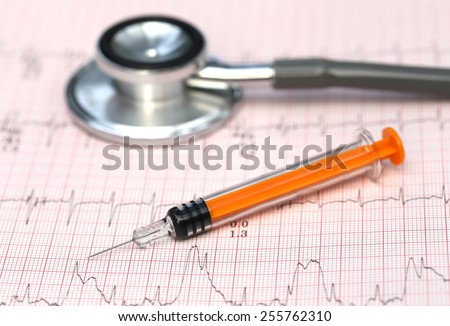 Close up of electrocardiograph with stethoscope and syringe - stock photo