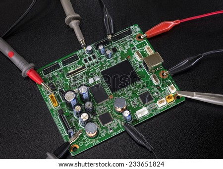 Close-up of electronic circuit board with several microchips with tools and wires around - stock photo