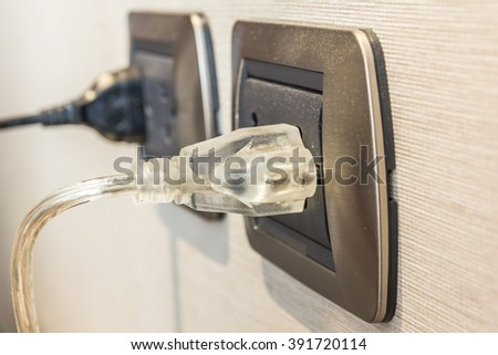 Close up of electronic transparent  power plug plugged in a wall socket. - stock photo
