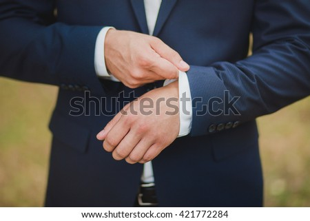 Close-up of elegance male hands wearing modern suit. Man dressed in blue suit and white shirt standing over green nature background. Groom, graduate or businessman. Formal style of clothes. - stock photo