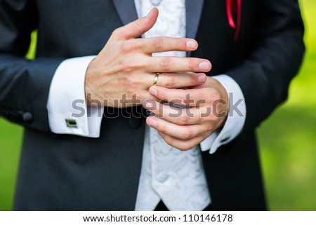 Close-up of elegance man hands with ring, and cufflink - stock photo