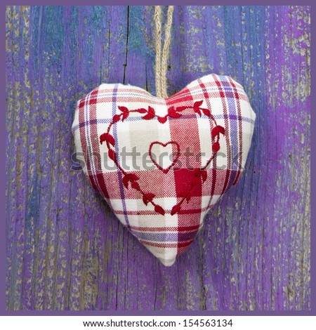 Close-up of embroidered heart shape on purple wooden surface. - stock photo