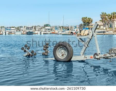 Close up of empty boat trailer in water at the harbor. Used to transport small boats in and out of the water. View of yachts docked in marina in background.  - stock photo
