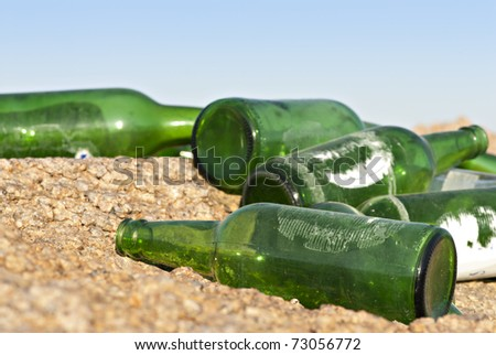Close-up of empty green glass bottles, dumped on a rocky ground. South Sinai, Egypt. - stock photo