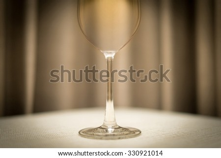 Close-up of empty wineglass on table with white tablecloth. Shiny single glass. Blurred brown drapery in background.
